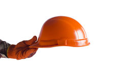 Hand holding out the construction orange helmet. Royalty Free Stock Images