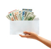 Hand holding out an envelope full of euro and dollars money Stock Photos