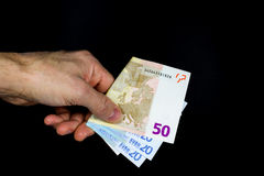 Hand holding out some banknotes. On a dark background Stock Image