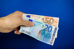 Hand holding out two banknotes Royalty Free Stock Photography