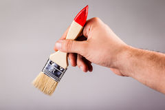 Hand holding a paintbrush Royalty Free Stock Photos