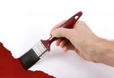 Hand holding paintbrush painting wall red Royalty Free Stock Photos