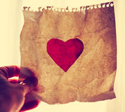 Hand holding a painted  paper heart up to the sun during suns Royalty Free Stock Photos