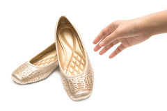 hand holding pair of beige female shoes Royalty Free Stock Photo