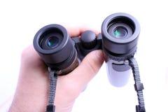 Hand holding pair of binoculars isolated on white Stock Photo