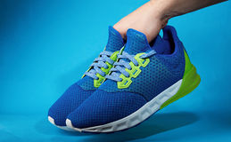 Hand holding pair of new running shoes. Isolated on blue background. Become sporty life royalty free stock images