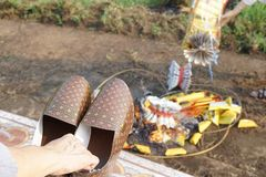 A Hand holding a pair of paper shoe. Burning of joss money and p stock image