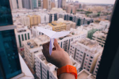 Hand holding paper airplane above city Stock Images