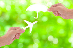 Hand holding a paper airplane and umbrella on green background,. Travel Insurance Stock Photo