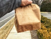 Hand holding brown paper bag Stock Images