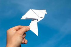 Hand holding paper bird against blue sky Royalty Free Stock Images