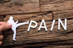 Hand Holding Paper Businessman Kicking Word Pain. Closeup of hand holding paper businessman kicking word pain on wood stock image