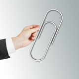 Hand holding Paper clip Royalty Free Stock Images