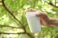 Hand holding paper coffee cup with green leaves background Stock Photography