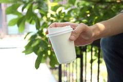 Hand holding paper coffee cup with office background Stock Image