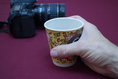 Hand holding a paper cup of coffee. Camera is in the background royalty free stock photography