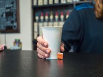 Hand holding a paper Cup of tea. Male hand with paper cup on the bar, counter with blurred background, soft focus.  Stock Photos