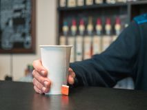 Hand holding a paper Cup of tea. Male hand with paper cup on the bar with blurred background. Bar counter with bottles. In soft focus Royalty Free Stock Images