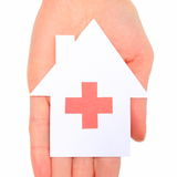 Hand holding paper house with red cross sign Royalty Free Stock Photos