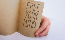 Hand holding a paper with label Free your mind. Hand holding a sheet of paper on a white background royalty free stock photography