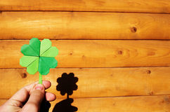 Hand holding paper origami green shamrock Stock Photo