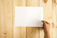 Hand holding paper over wooden background. Empty for text royalty free stock image