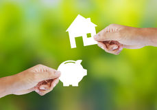 Hand holding paper piggy bank and house shape Stock Images