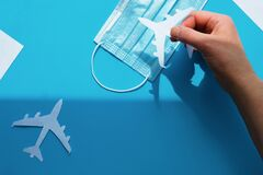 Free Hand Holding Paper Plane Over Face Mask Takes It From Shadow To Light. Air Travel Resumes After Travel. Vacations Stopped And Royalty Free Stock Image - 182437516