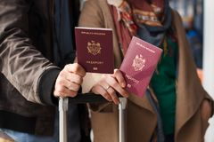 Couple Hand holding Passport . Traveler with Luggage Travel concept. People tourism. Biometric Moldavian passports. Hand holding Passport Traveler with Luggage Stock Photography