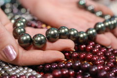 Hand holding pearls of many colors. Female holding strands of pearls Royalty Free Stock Photo