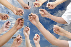 Hand holding pen. Many hand holding pen, with blue sky Royalty Free Stock Image