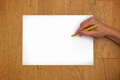 Hand holding pen on blank paper sheet on a table. Hand holding pen on a blank white paper sheet (in horizontal position) on a worn wooden table surface, viewed royalty free stock photo