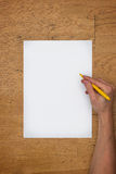 Hand holding pen on blank paper sheet on a table. Hand holding pen on a blank white paper sheet on a worn wooden table surface, viewed from above stock images