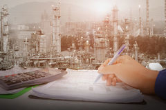 Monitoring. Hand holding pen for check list on paper page, Inspection and operation in control room concept, Operation petrochemical plant with control room Royalty Free Stock Photography