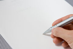 Hand holding pen with document Stock Image