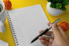 Hand holding a pen on notebook. royalty free stock photo