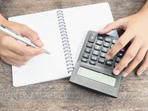 Hand holding pen with notepad and calculator Stock Photos