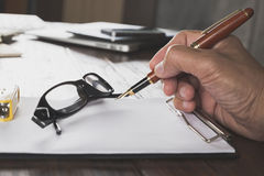 hand holding pen with notepad and eyeglasses on office desk Royalty Free Stock Photo