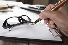 hand holding pen with notepad and eyeglasses on office desk Stock Photos
