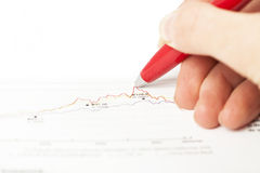 Hand holding pen over business graph Stock Photo