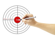 Hand holding a pen pointing to bull`s eye Royalty Free Stock Image