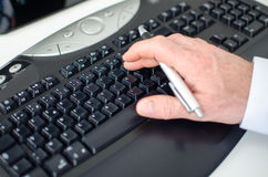 Hand holding a pen and typing on a keyboard Stock Photo