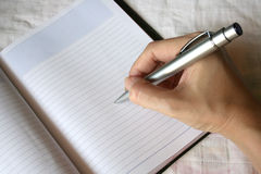 Hand holding pen writing on note book. Woman's hand holding pen writing on note book Royalty Free Stock Photography