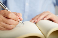 Hand holding a pen and writing in notebook,Close up Stock Image