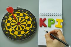 Hand holding pencil and colorful alphabet KPI with dartboard as. Goals or Target concept Stock Images