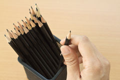 Hand holding a pencil from pencil case. Hand holding a pencil from case on wooden background Royalty Free Stock Photo