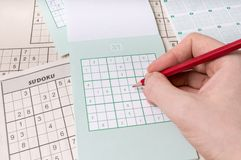 Hand is holding pencil and is solving sudoku crossword with numers Royalty Free Stock Images