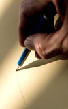 Hand holding pencil to write on the paper in shadow Stock Images