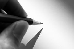 Hand holding pencil to write on the paper in shadow Royalty Free Stock Photos