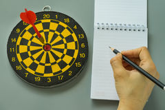 Hand holding pencil on white note paper with dartboard as Goals Royalty Free Stock Photo